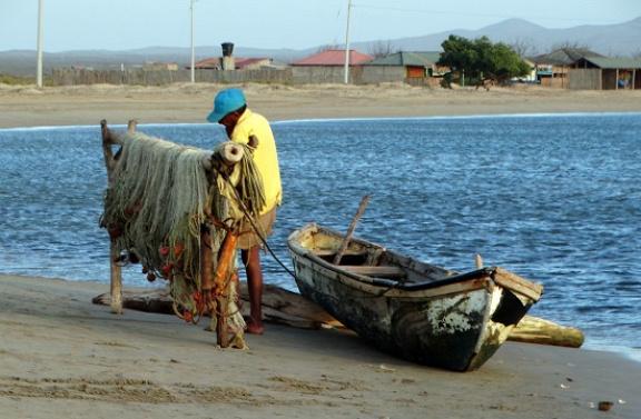 Halász bíbelődik a hálójával az érdektelen tengerparton