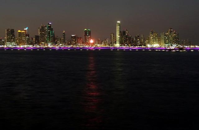 Éjszakai látkép a felhőkarcolók előtt futó, oceánba épített autópályával