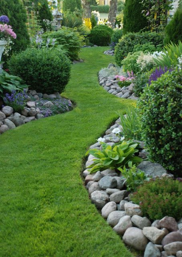 Stone border. Love the winding grass pathway. Not too much to mow. Soft meandering path by which to enjoy the garden.